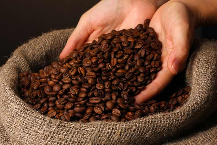 hands holding coffee beans above bag