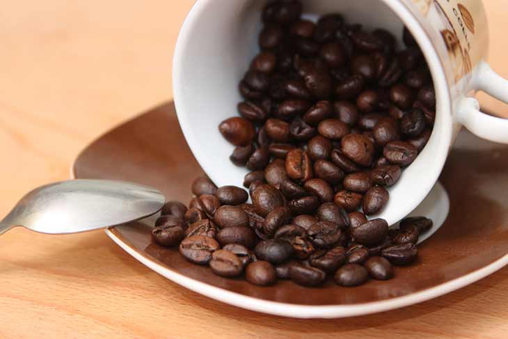 cup of spilt roasted coffee beans