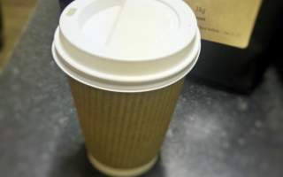 Pollards-disposable-coffee-cup-craft-cup-with-white-lid-pollards-puccini-blend-coffee-beans-in-the-background.