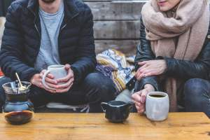 couple-sat-outside-coffee-shop-cosy-cups-scarves-jacket-chat-informal-table-hot-beverage-mug-hands-hold-position